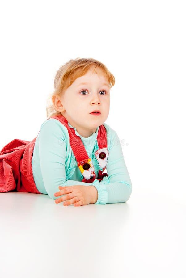 Een meisje in een rode kleding, het liggende stellen royalty-vrije stock afbeeldingen