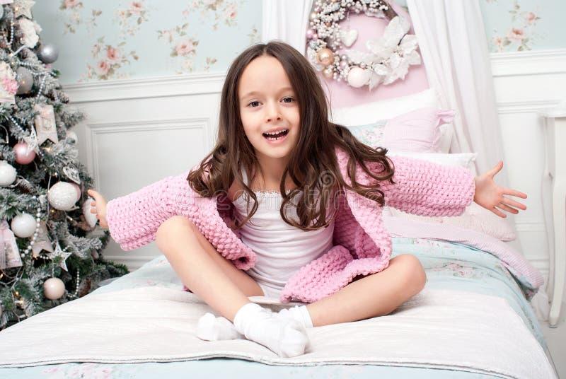 Een meisje in een roze breit cardigan in bed royalty-vrije stock afbeelding
