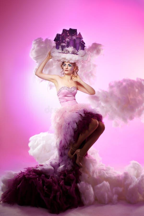 Een meisje in een weelderig slot van de wolkenlucht op het hoofd stock fotografie