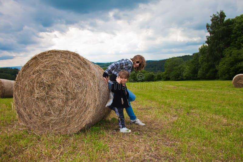 Een meisje en een jongen die een ronde bundel van stro duwen. royalty-vrije stock fotografie