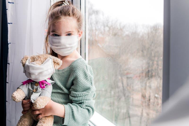 Een meisje en een speelgoedbeer in medische maskers in de buurt van het raam, kijkend naar de straat, de noodzaak om thuis te bli stock foto