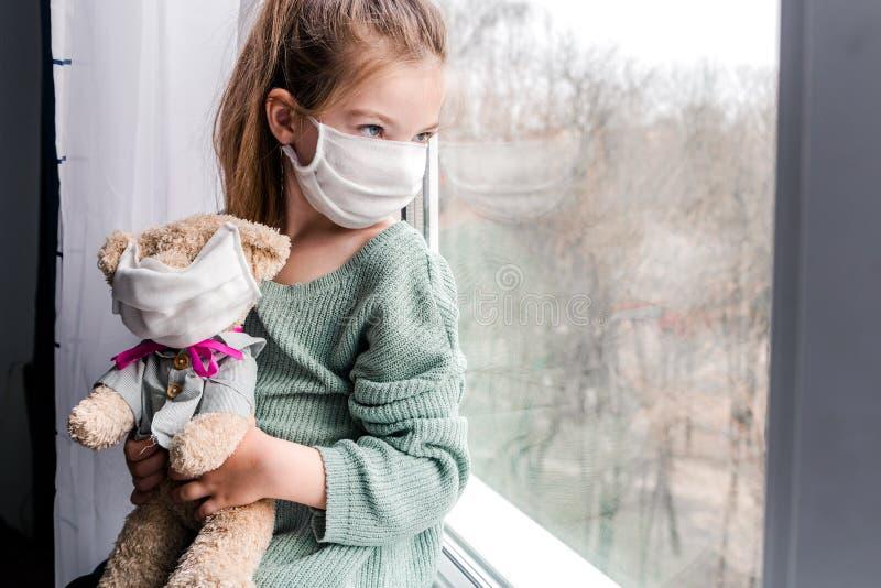 Een meisje en een speelgoedbeer in medische maskers in de buurt van het raam, kijkend naar de straat, de noodzaak om thuis te bli royalty-vrije stock afbeelding