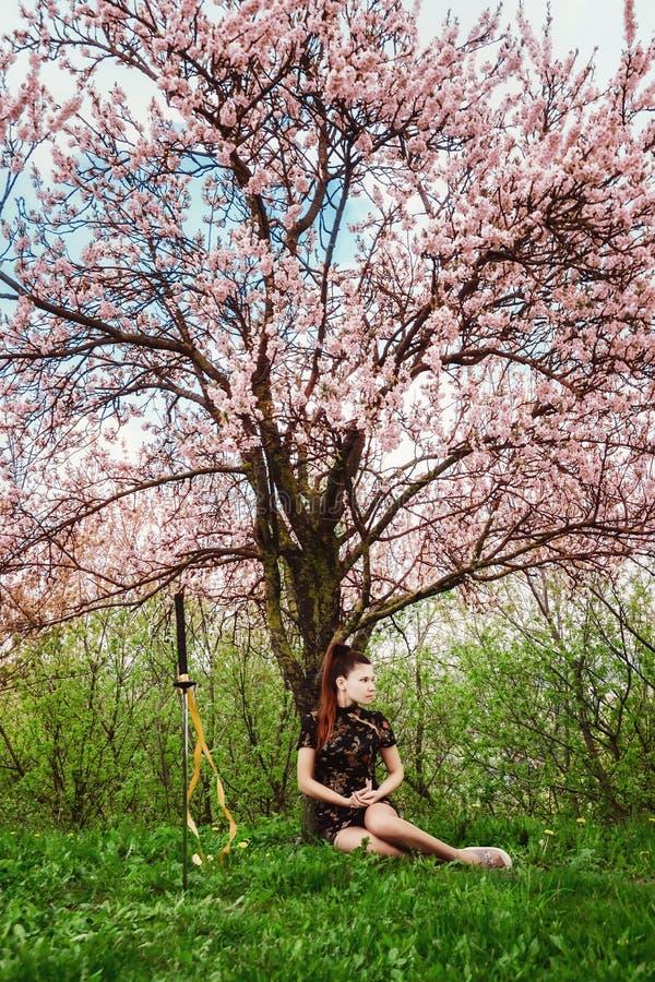 Een meisje en een zwaard onder bloeiende kers komen tot bloei stock foto