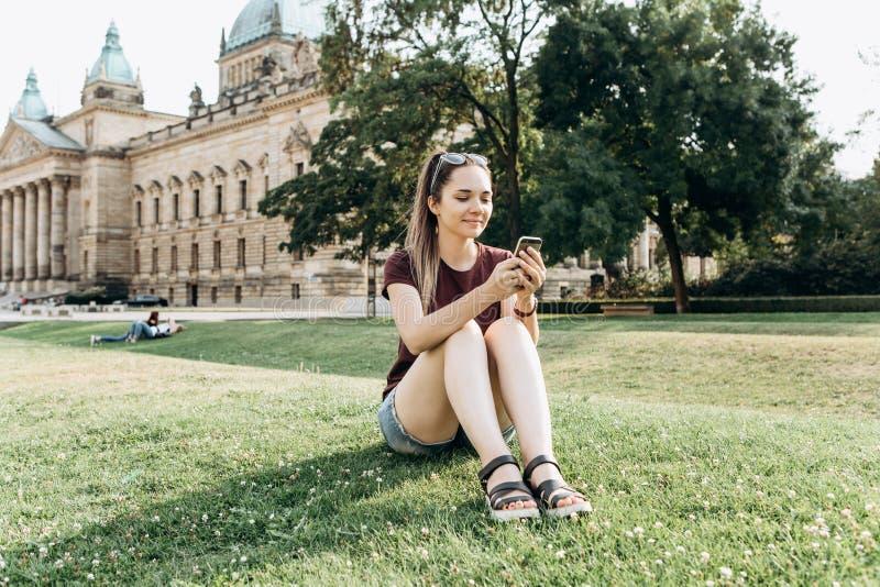 Een meisje gebruikt een mobiele telefoon stock foto