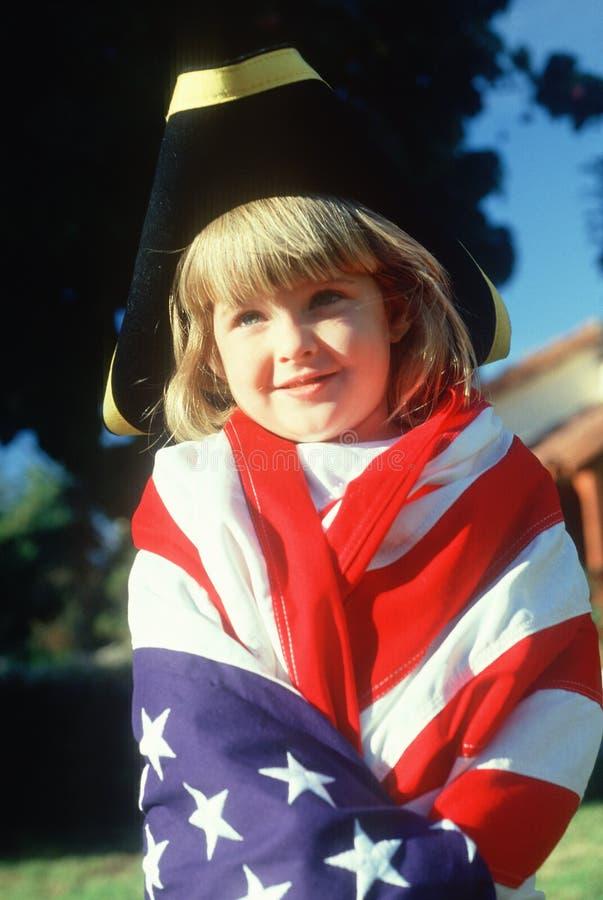 Een meisje gedrapeerd in een Amerikaanse vlag, stock fotografie