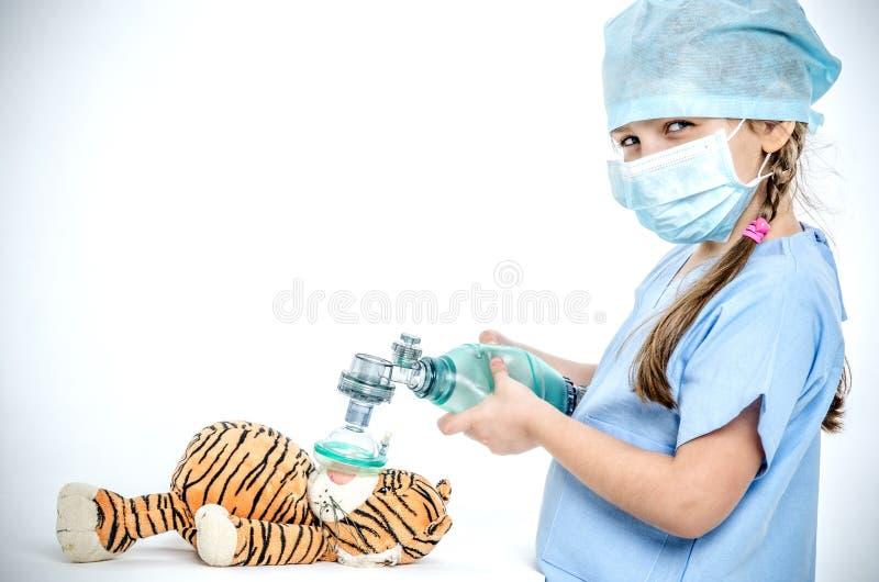 Een meisje gekleed in een chirurgisch kostuum houdt een ambassadeur over een stuk speelgoed tijger en maakt kunstlongventilatie stock afbeeldingen