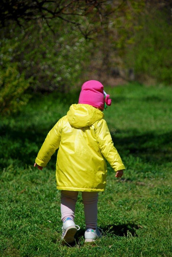 Een meisje in een gele regenjas die in het bos lopen royalty-vrije stock afbeelding