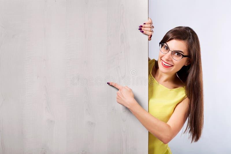 Een meisje in glazen richt met haar wijsvinger op een houten raad B stock foto's