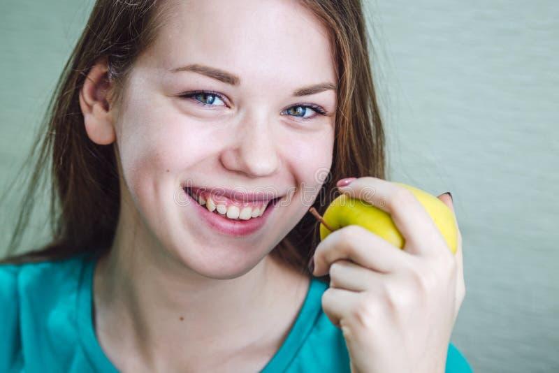 Een meisje glimlacht en houdt een appel in haar hand stock afbeeldingen