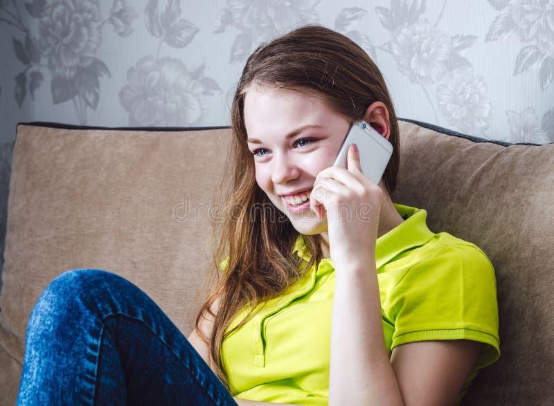 Een meisje glimlacht, spreekt en houdt mobiele telefoon stock afbeelding