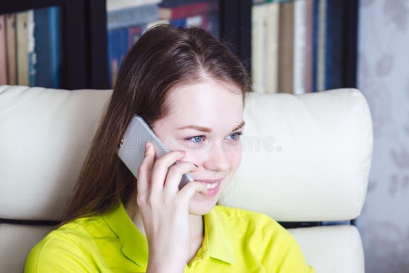 Een meisje glimlacht, spreekt en houdt mobiele telefoon royalty-vrije stock fotografie
