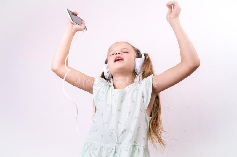 Een meisje in een groene t-shirt luistert aan muziek van een smartphone in grote witte hoofdtelefoons en zingt op een wit royalty-vrije stock afbeeldingen