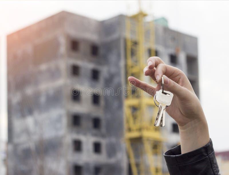 Een meisje in haar hand houdt de sleutels aan een flat op de achtergrond van een gebouwde huishypotheek stock afbeelding