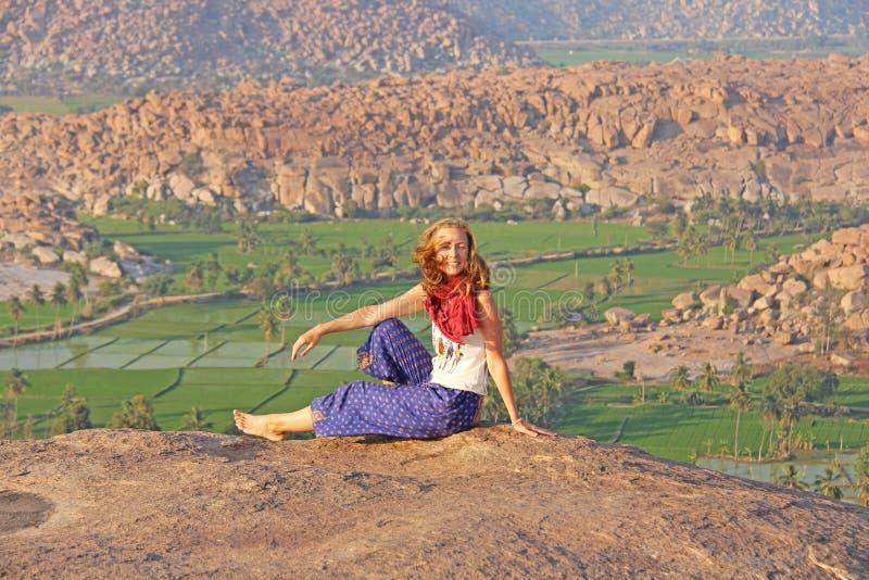 Een meisje in Hampi, zit en glimlacht op Anjaneya-Heuvel, Hanuman Temple Ontspan en rust, alleen met aard Padievelden of terrasse royalty-vrije stock fotografie