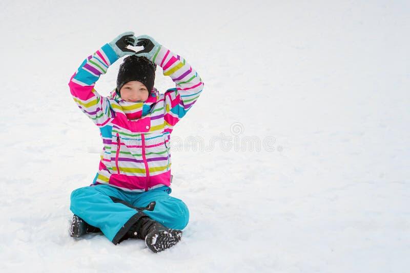 Een meisje in een heldere kleurrijke skiverbindingsdraad in een helder jasje zit, op de zaligheid en toont het hart met zijn hand royalty-vrije stock foto