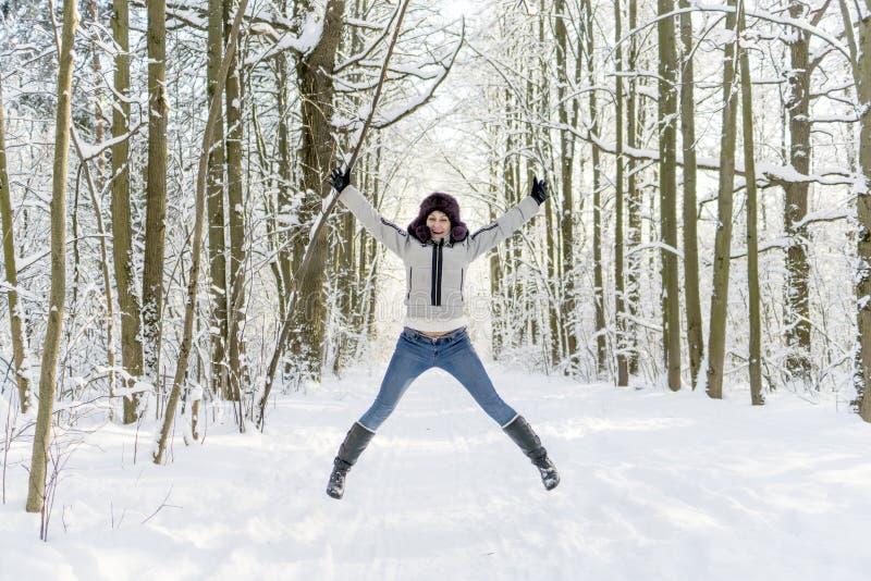 Een meisje in het hout springt omhoog Heel wat sneeuw royalty-vrije stock fotografie