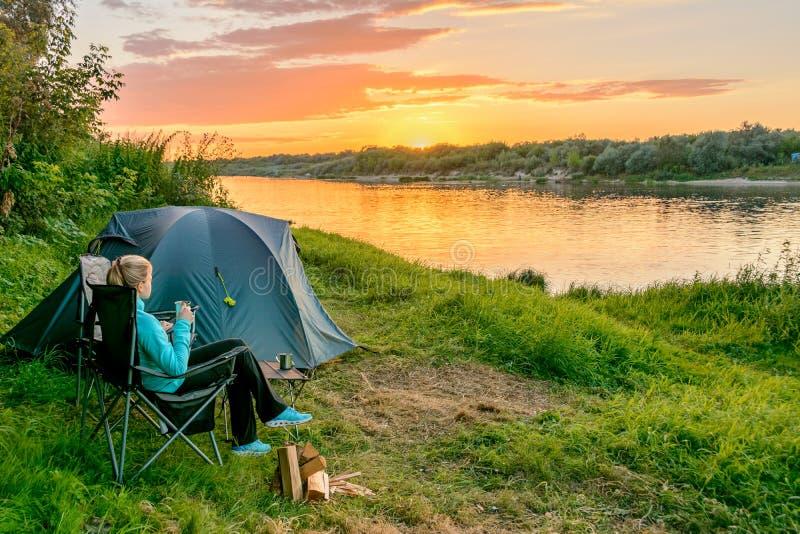 Een meisje in het kamperen met een toeristentent op de rivierbank Rusland stock foto's