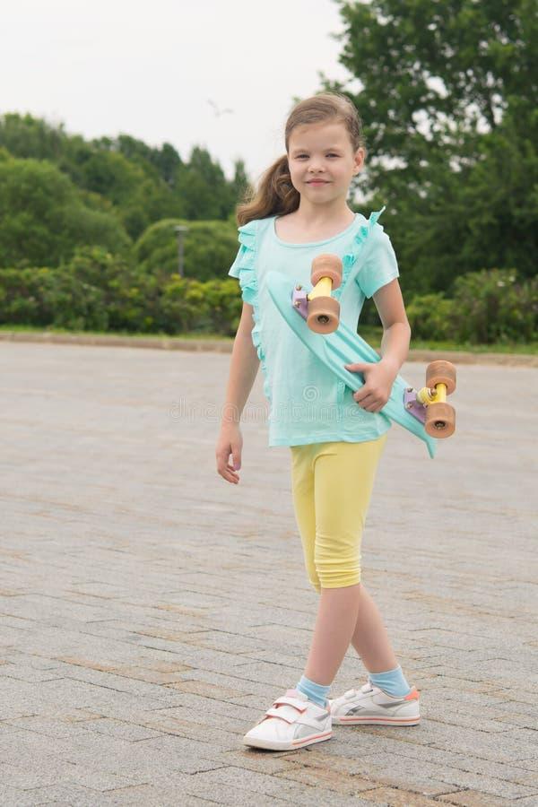 Een meisje in het park, op de achtergrond van aard, bevindt zich met een sportenraad in haar handen, op een steenbestrating royalty-vrije stock foto