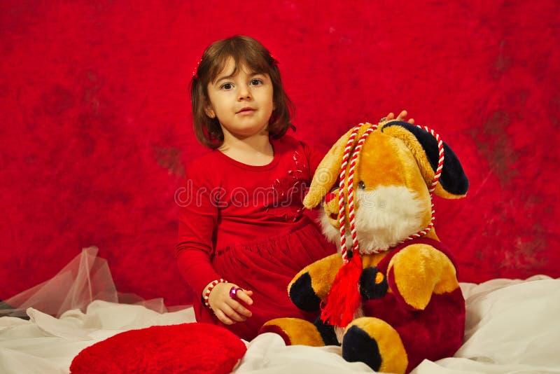 Een meisje in het rode spelen met het gevulde konijntjesstuk speelgoed stock afbeeldingen