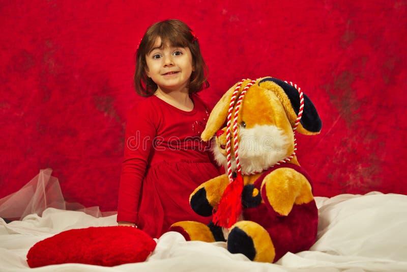 Een meisje in het rode spelen met het gevulde konijntjesstuk speelgoed royalty-vrije stock afbeelding