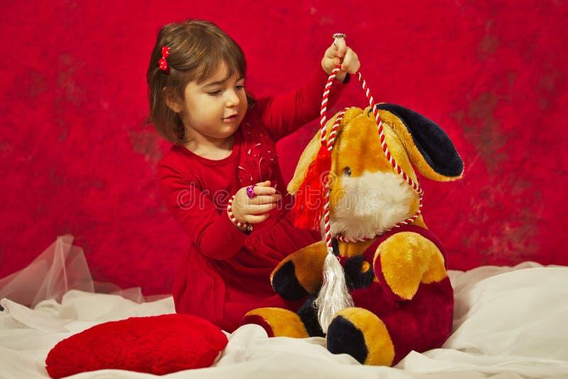 Een meisje in het rode spelen met het gevulde konijntjesstuk speelgoed stock foto's