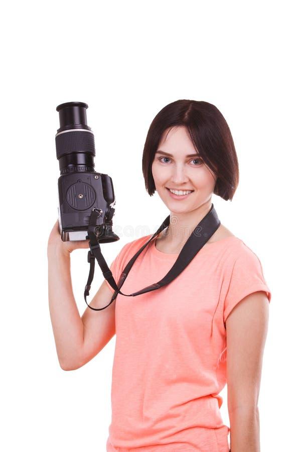 Een meisje houdt een camera in haar hand en kijkt aan de kant op een witte achtergrond royalty-vrije stock afbeelding