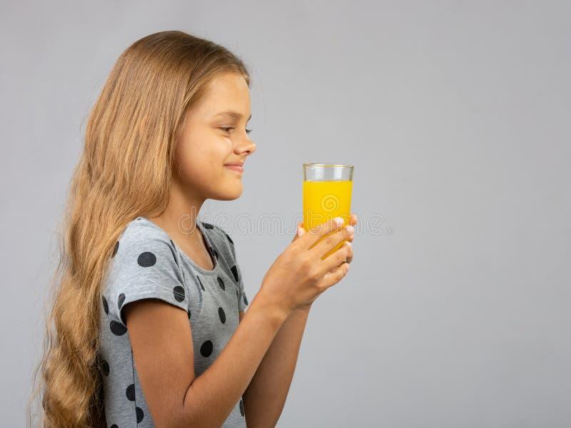Een meisje houdt een glas sap in haar handen met twee handen, profielmening royalty-vrije stock foto's