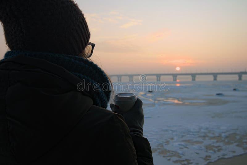 Een meisje houdt een koffiedocument kop in haar handen en let de winter op zonsopgang op de banken van de Dnieper-Rivier in Kyiv, stock fotografie