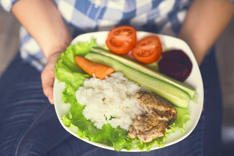Een meisje houdt een plaat met groenten en kippenvlees met kruiden stock afbeelding