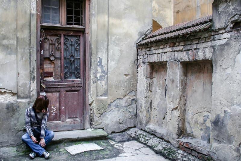 Een meisje in jeans, een gestreepte sweater en tennisschoenen zit op de drempel door de houten deur van een zeer oud huis stock afbeelding