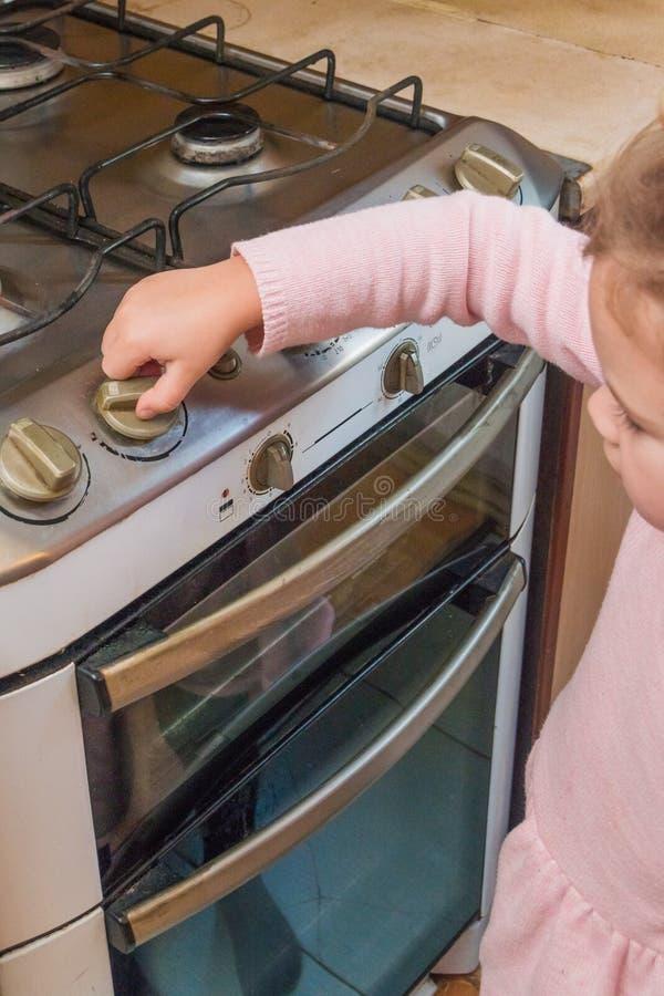 Een meisje, een kind omvat een gasfornuis in afwezigheid van volwassenen, t stock afbeelding