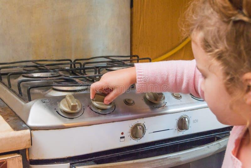 Een meisje, een kind omvat een gasfornuis in afwezigheid van volwassenen, t stock fotografie