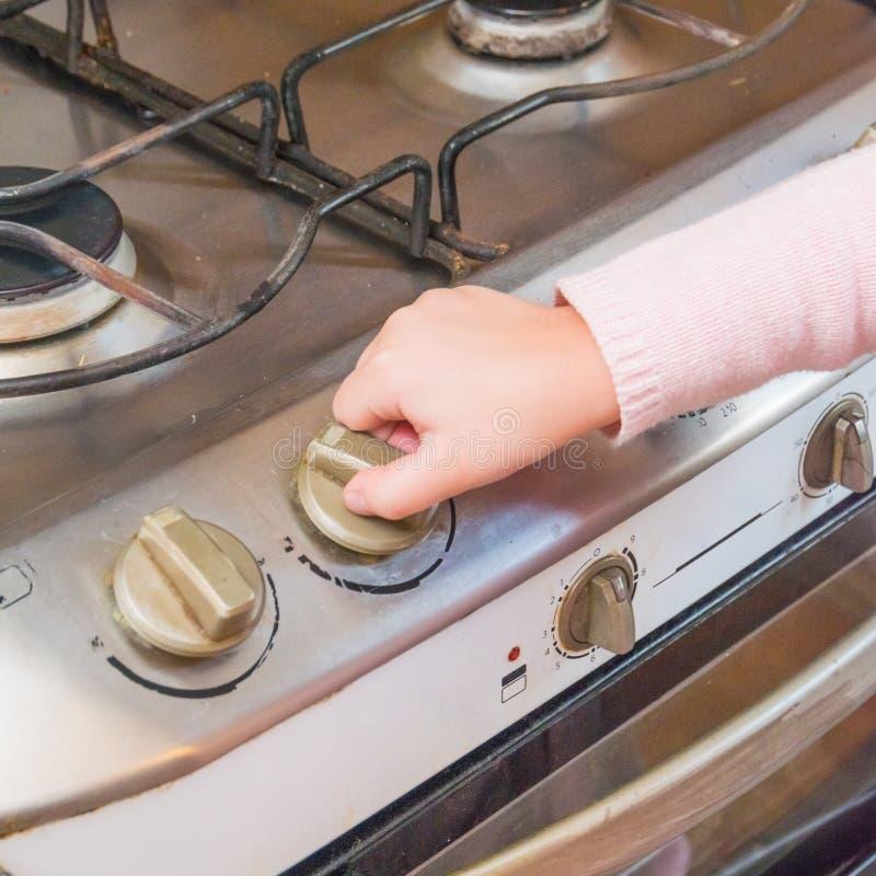 Een meisje, een kind omvat een gasfornuis in afwezigheid van volwassenen, t stock foto's