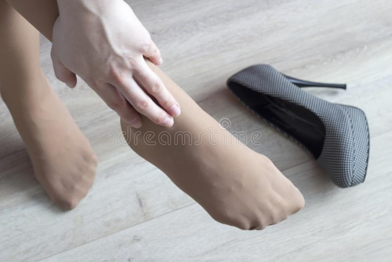 Een meisje klampt zich aan haar been, moeheid van haar hielen, hoge hielen, pijn in haar benen vast, close-up, persoon royalty-vrije stock foto