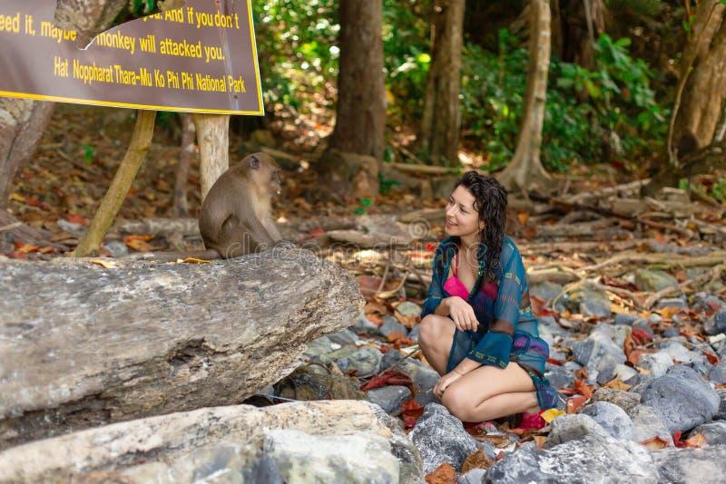 Een meisje in een koele zwempak en een pareo die aan apen op een tropisch aapstrand spreken stock fotografie