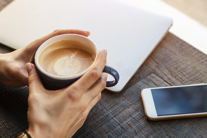 Een meisje in een koffie drinkt de kunst van de koffiecappuccino latte, op tabl royalty-vrije stock foto