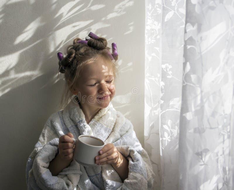 Een meisje in krulspelden in een robe drinkt van een mok dichtbij de muur royalty-vrije stock foto's