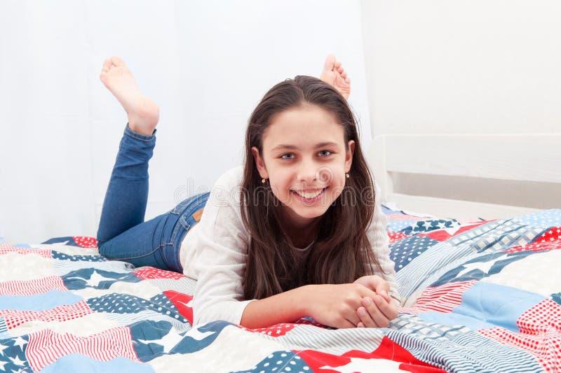 Een meisje ligt op een bed stock afbeelding