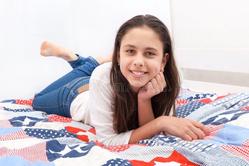 Een meisje ligt op een bed stock foto's