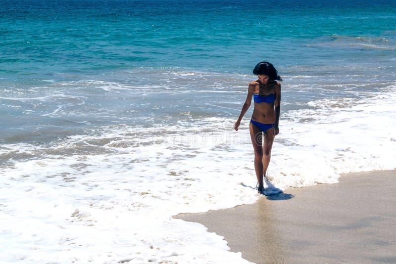 Een meisje loopt op het strand stock foto