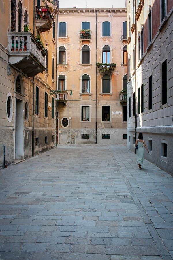 Een meisje loopt op een straat in Venetië stock foto