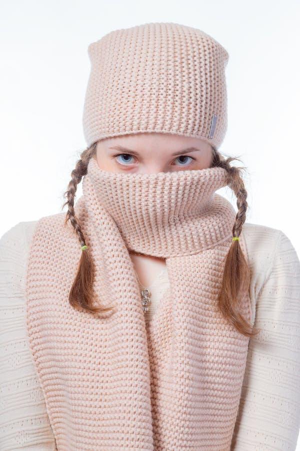 Een meisje met blauwe ogen en vlechten verbergt haar gezicht achter een gebreide sjaal Starende blik in de camera royalty-vrije stock foto's