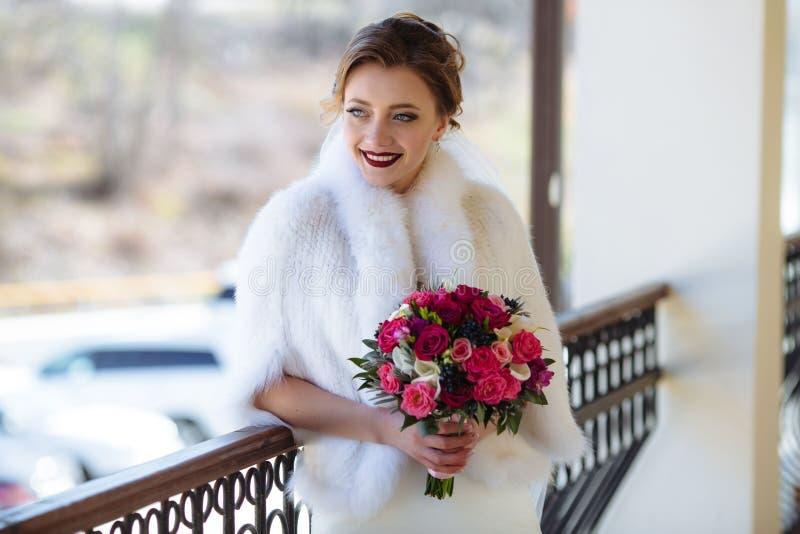 Een meisje met een boeket van een bruid bevindt zich dichtbij de houten gesneden leuning en kijkt ruim weg glimlachend Een vrouw  stock foto
