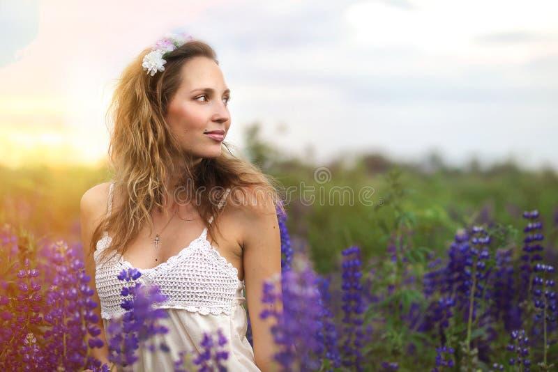 Een meisje met een boeket van purpere lupines stock foto's