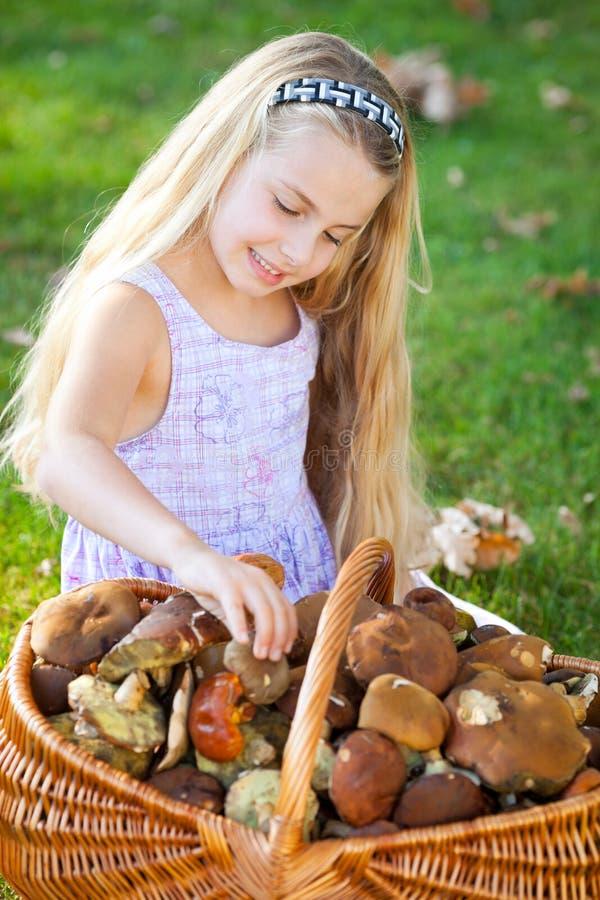 Een meisje met een mand vulde met paddestoelen royalty-vrije stock afbeeldingen