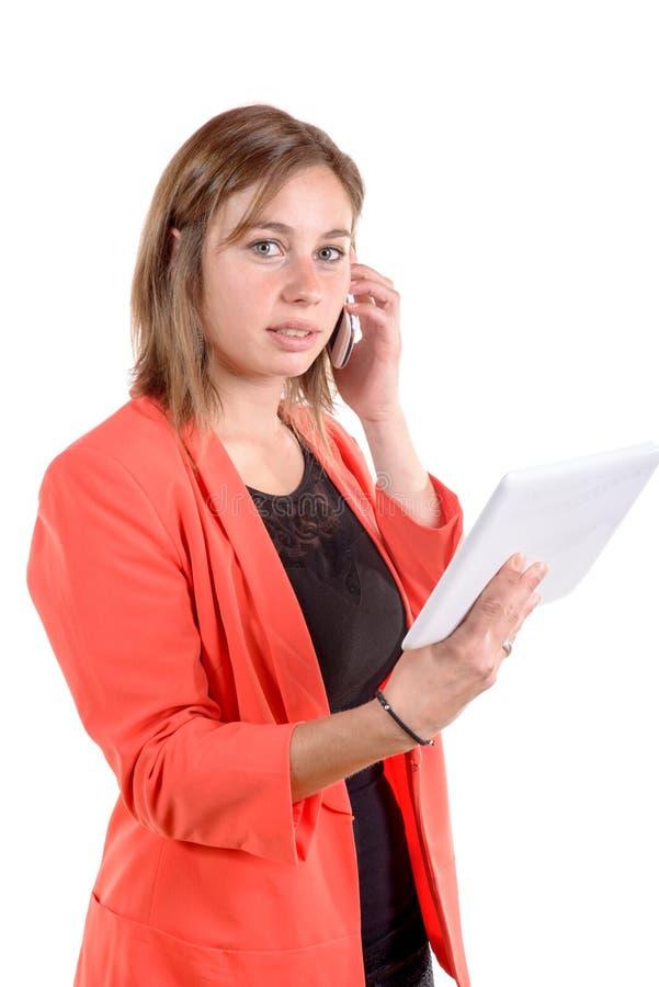 Een meisje met een rood jasje houdt een digitale tablet en een telefoon stock foto
