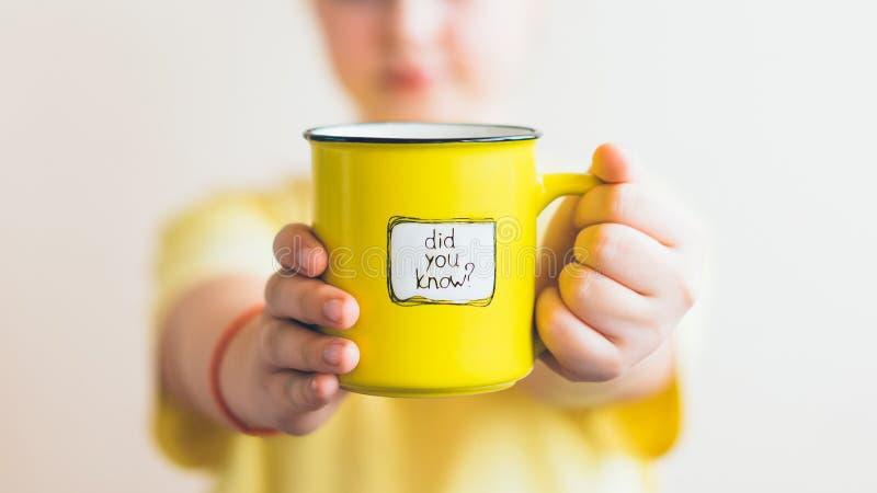 Een meisje met een gele kop in haar hand, waarop werd geschreven u wist het royalty-vrije stock foto's