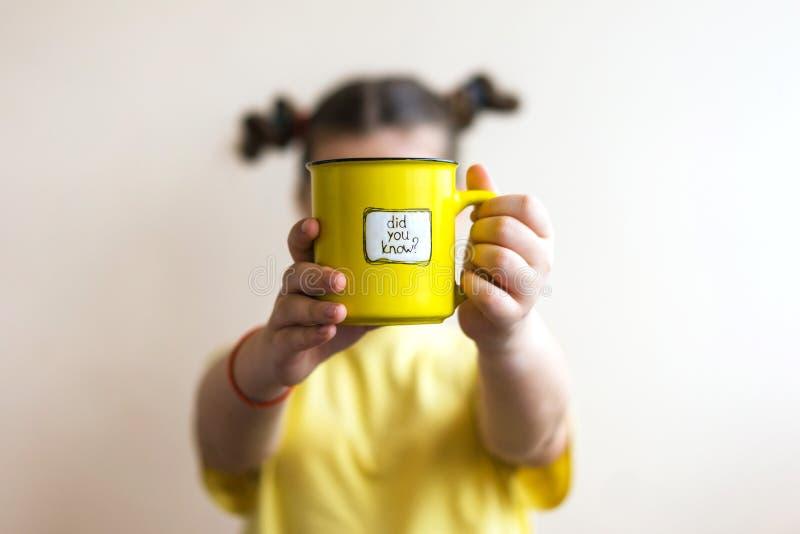 Een meisje met een gele ring in haar hand, waarop werd geschreven u wist het stock foto's