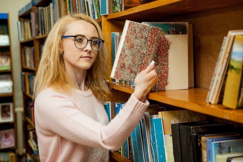 Een meisje met glazen kiest een boek in de bibliotheek stock afbeelding