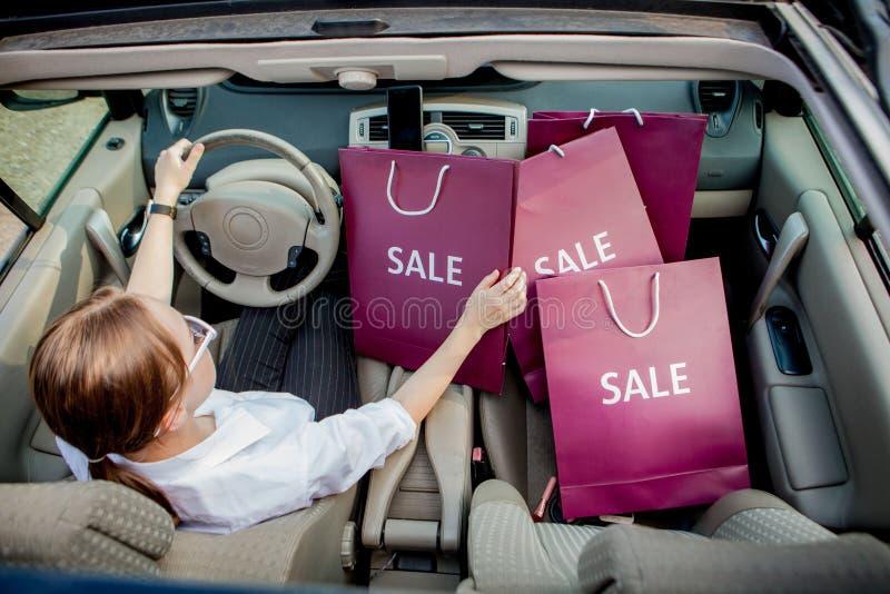 Een meisje met het winkelen zakken drijft een auto, concept kortingen en winkelt, hoogste mening royalty-vrije stock foto's